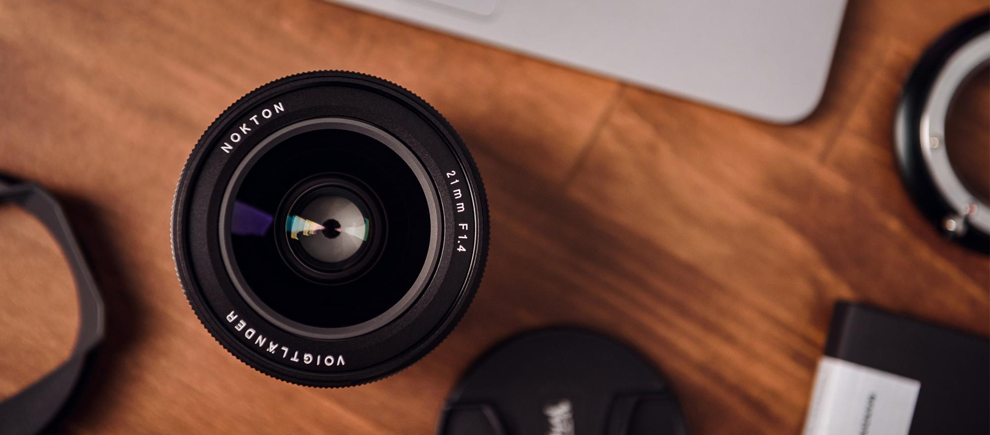 Obiektyw Voigtlander Nokton 21 mm f/1,4 z mocowaniem Leica M na biurku wraz z akcesoriami