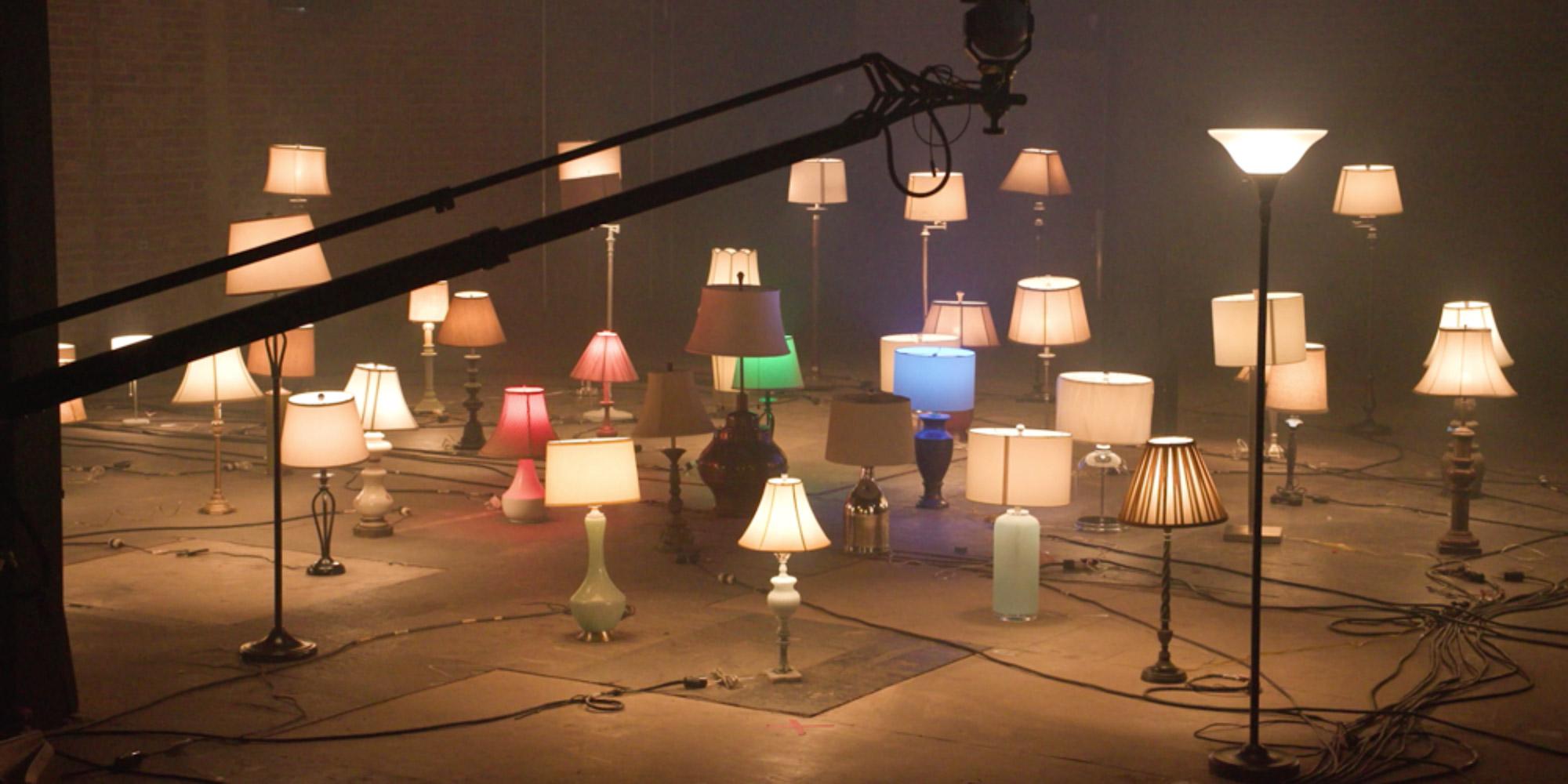 Kilkanaście lamp o różnych rozmiarach i stylu stojących na podłodze