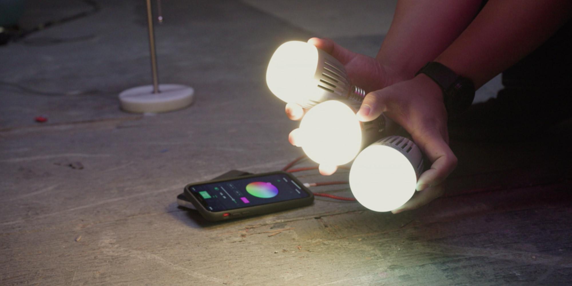 Trzy żarówki LED Aputure Accent B7c trzymane w dłoniach