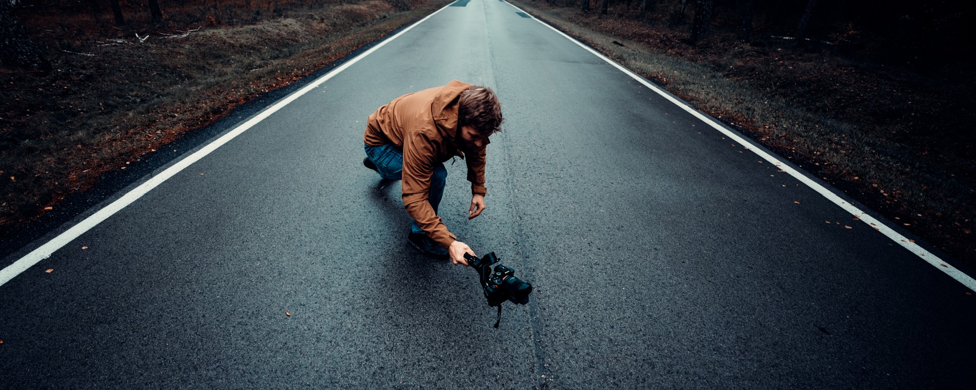 Zdjęcie - osoba na środku drogi, kucająca, trzymająca w ręku gimbala i filmująca coś z niskiej perspektywy