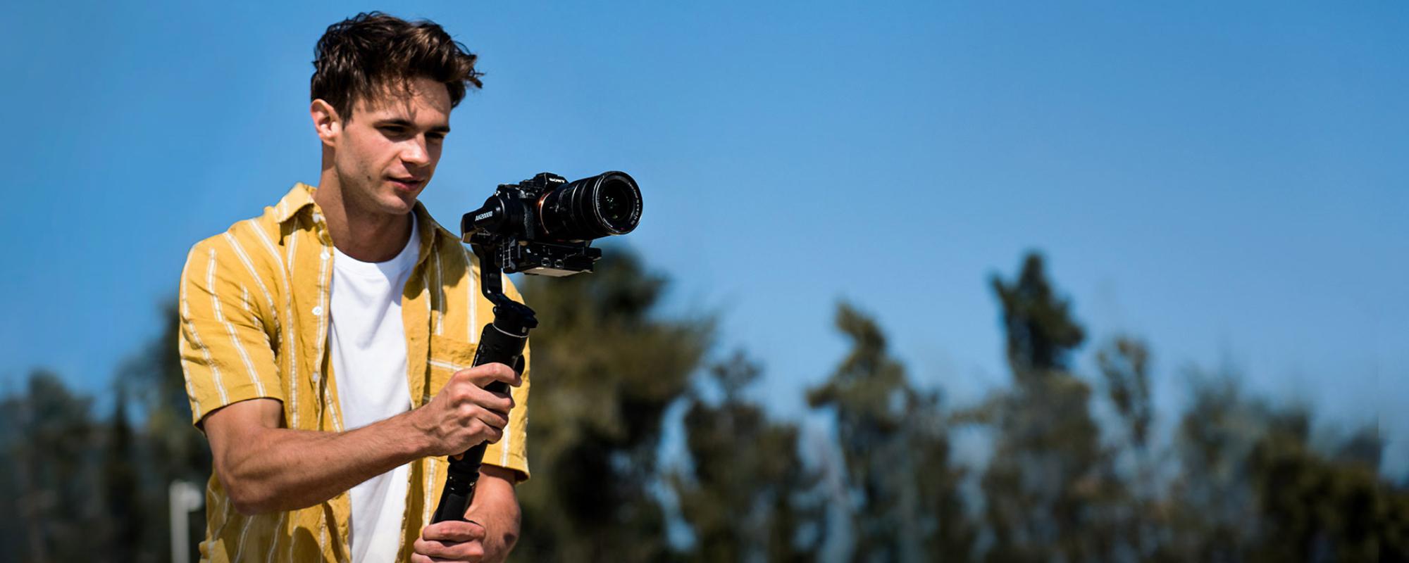 Męższczyzna nagrywajacy swoim aparatem umieszczonym na gimbalu AK2000S