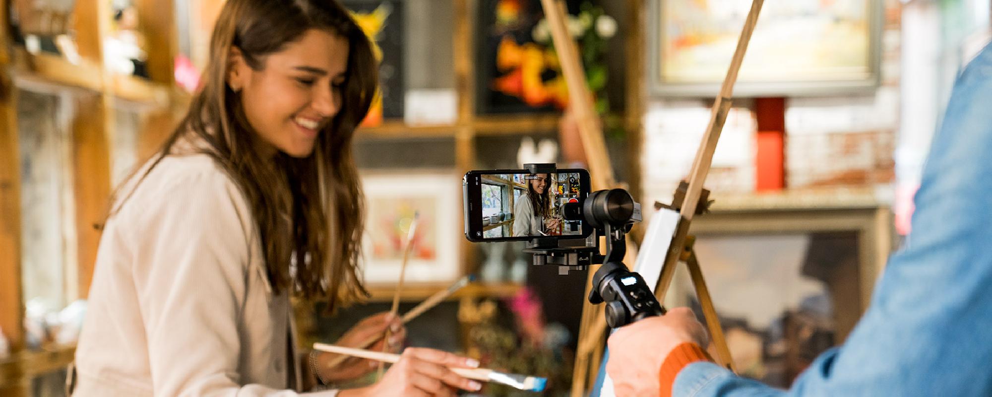 Dziewczyna maluje obraz będąc filmowana smartfonem na gimbalu FeiyuTech G6 Max