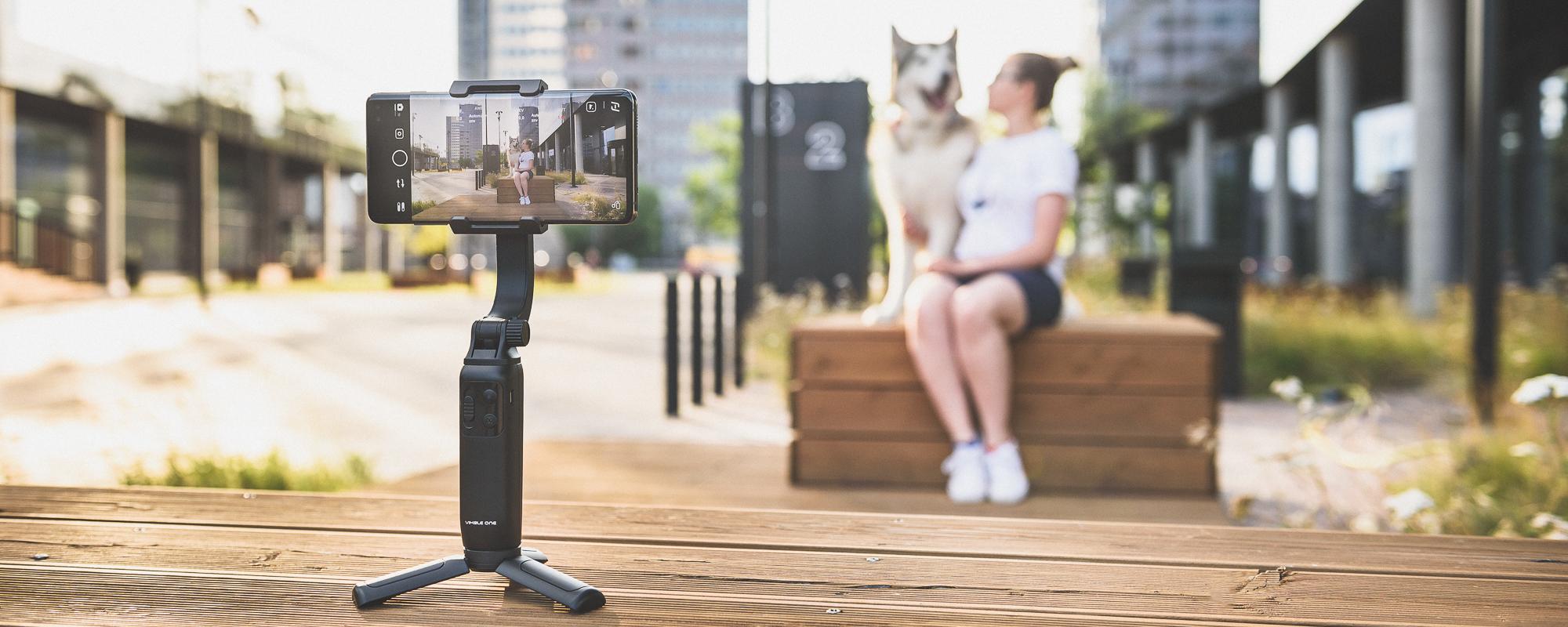 Gimbal nagrywa timelapse dziewczyny siedzacej z psem z panoramą miasta w tle