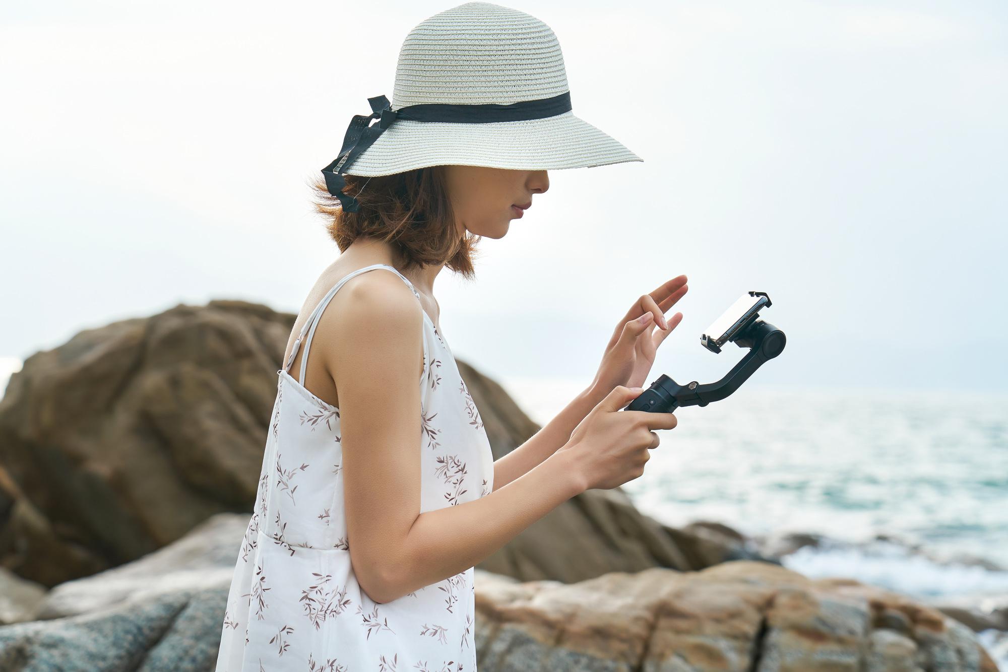 Dziewczyna nagrywa film smartfonem, który umieszczony jest na gimbalu