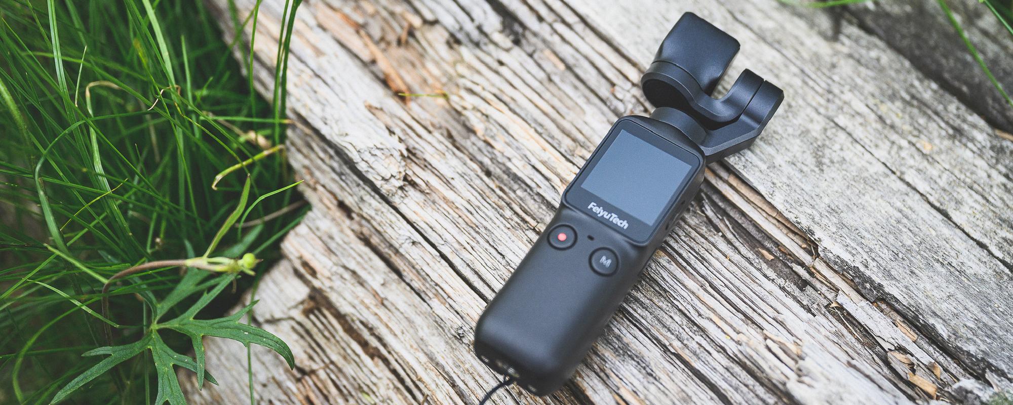 Zdjęcie pokazujące kamerę na drewnianym pniu - Kamera FeiyuTech Feiyu pocket idealnie nada sie na wyprawy w góry