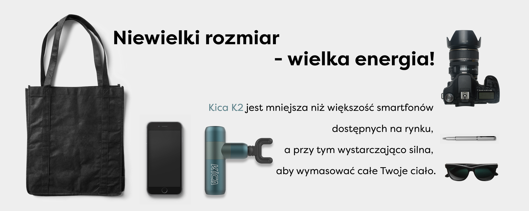 Grafika przedstawiająca masażer Kica K2 na tle smartfona, aparatu, długopisu i okularów przeciwsłonecznych. Jej rozmiar jest porównywalny do powyższych przedmiotów