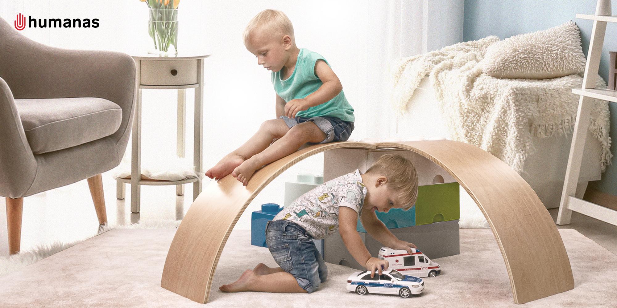Dwóch małych chłopców bawi się deską do balansowania Humanas BoardOne w dużym pokoju z meblami