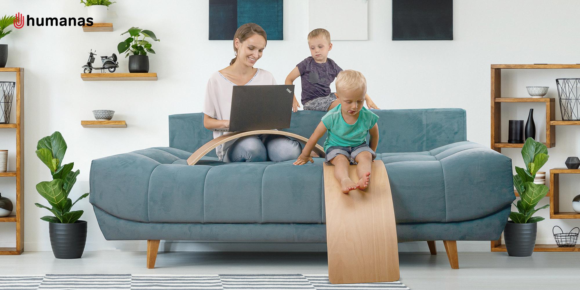 Dwóch małych chłopców i ich mama bawi się deską do balansowania Humanas BoardOne w dużym pokoju z meblami