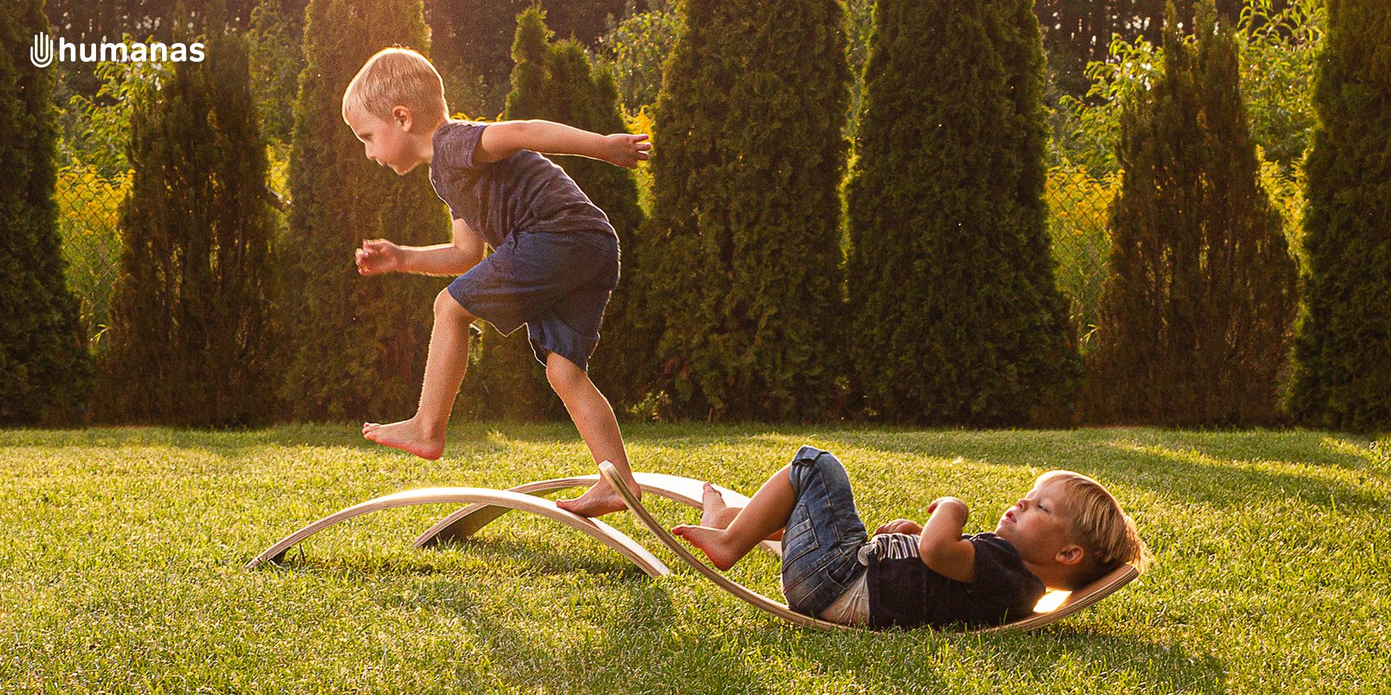 Dwóch małych chłopców bawi się deską do balansowania Humanas BoardOne w ogrodzie