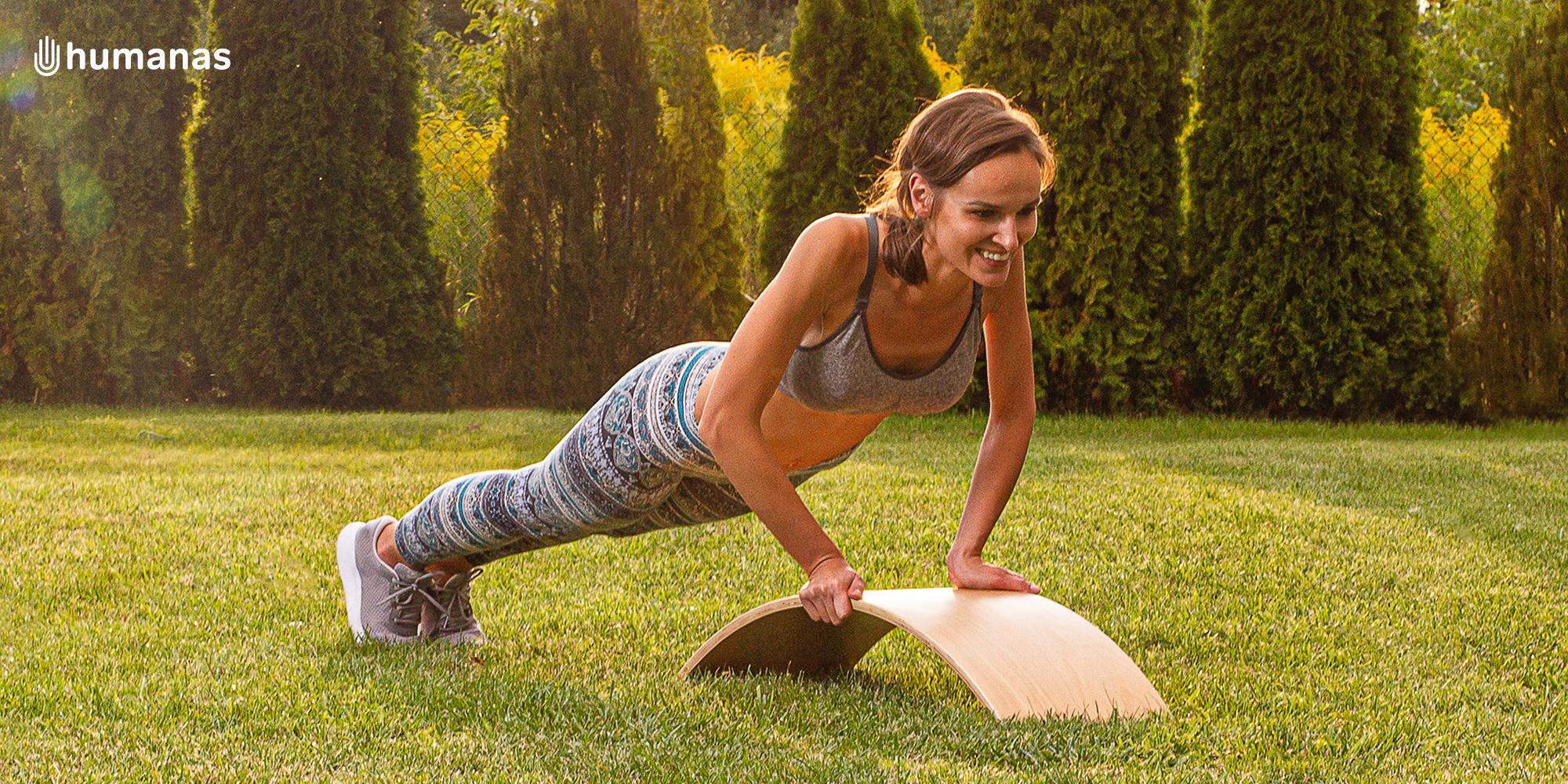 Młoda kobieta wykonuje ćwiczenia wzmacniające mięśnie przy użyciu deski do balansowania Humanas BoardOne