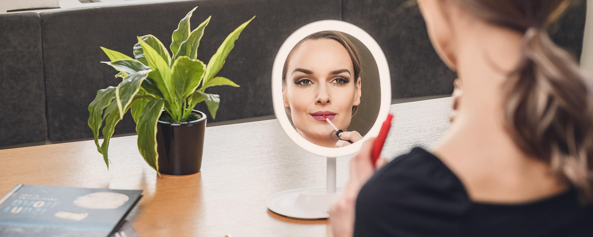 Młoda kobieta robi makijaż przed lusterkiem z oświetleniem LED