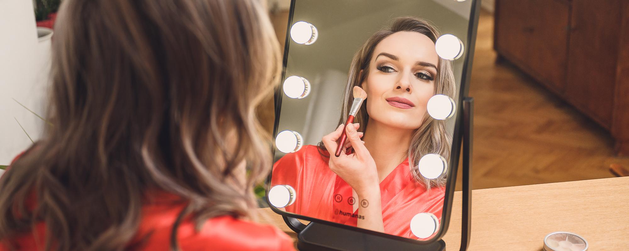 Młoda kobieta robi makijaż przed lustrem z oświetleniem LED
