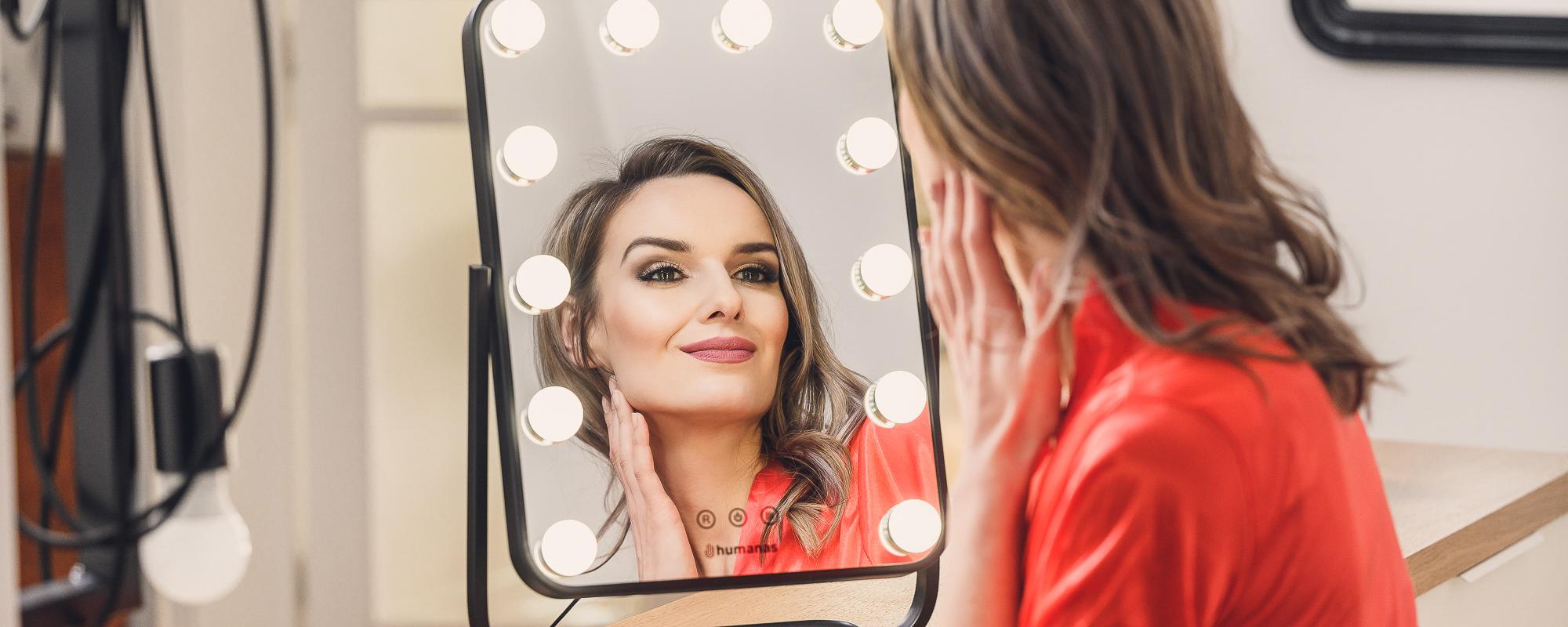 Młoda kobieta przegląda się w lustrze z oświetleniem LED