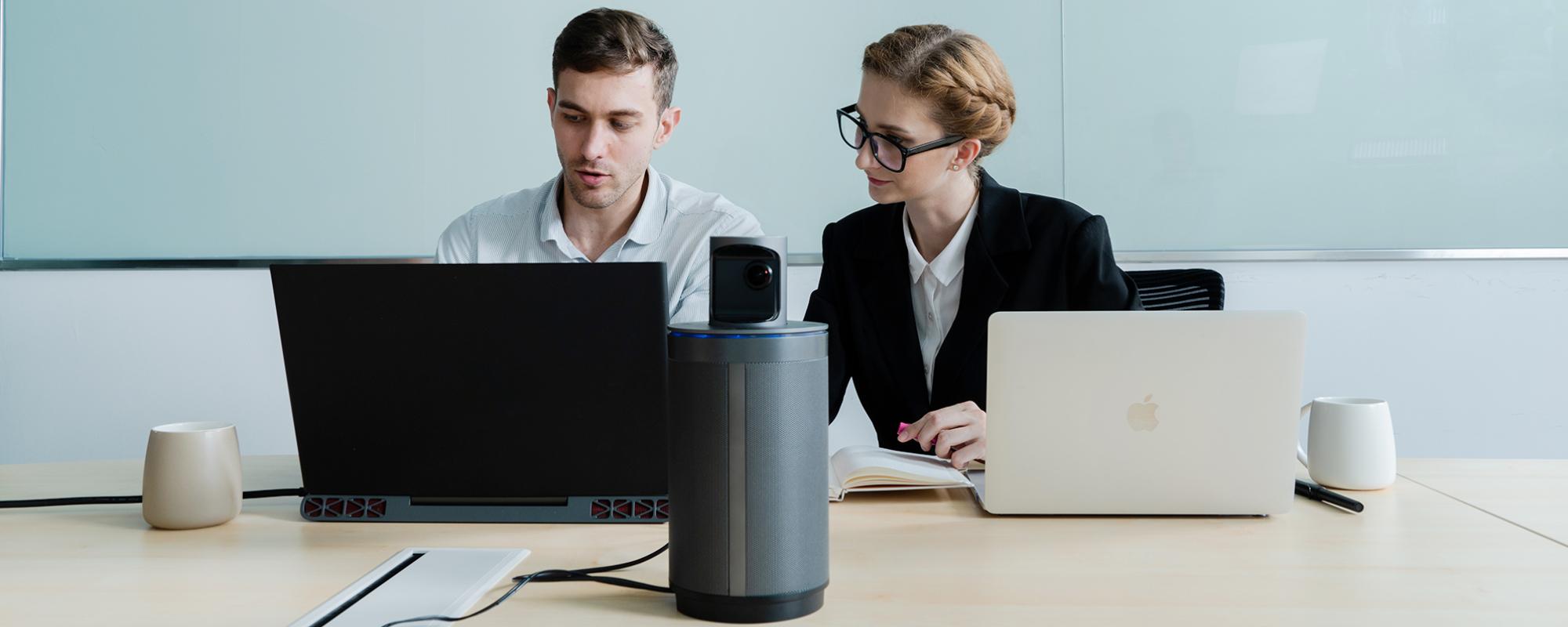 Kobieta i mężczyzna pracujący na laptopach z kamerą konferencyjną Kandao Meeting 360