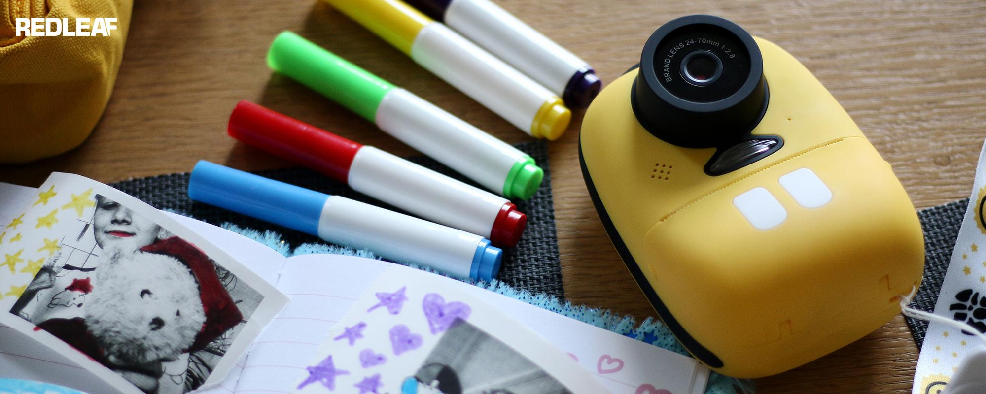 Aparat fotograficzny z drukarką dla dzieci Redleaf BOB leżący na biurku razem z kolorowymi mazakami