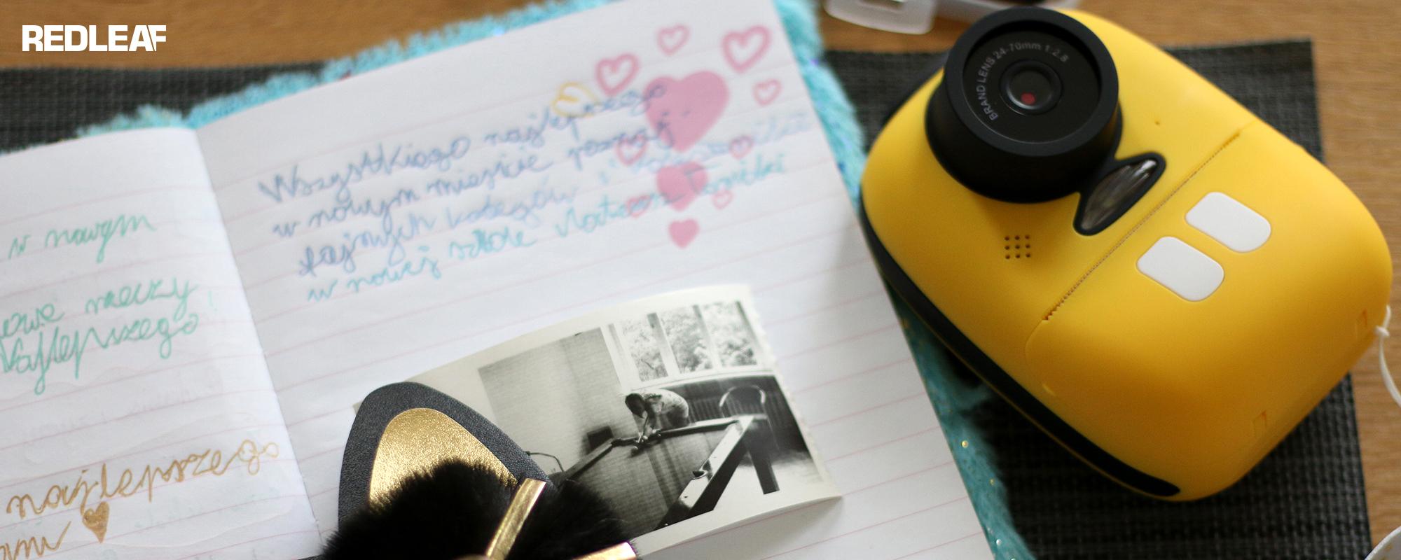 Aparat fotograficzny z drukarką dla dzieci Redleaf BOB położony na blacie biurka z zeszytem w linię