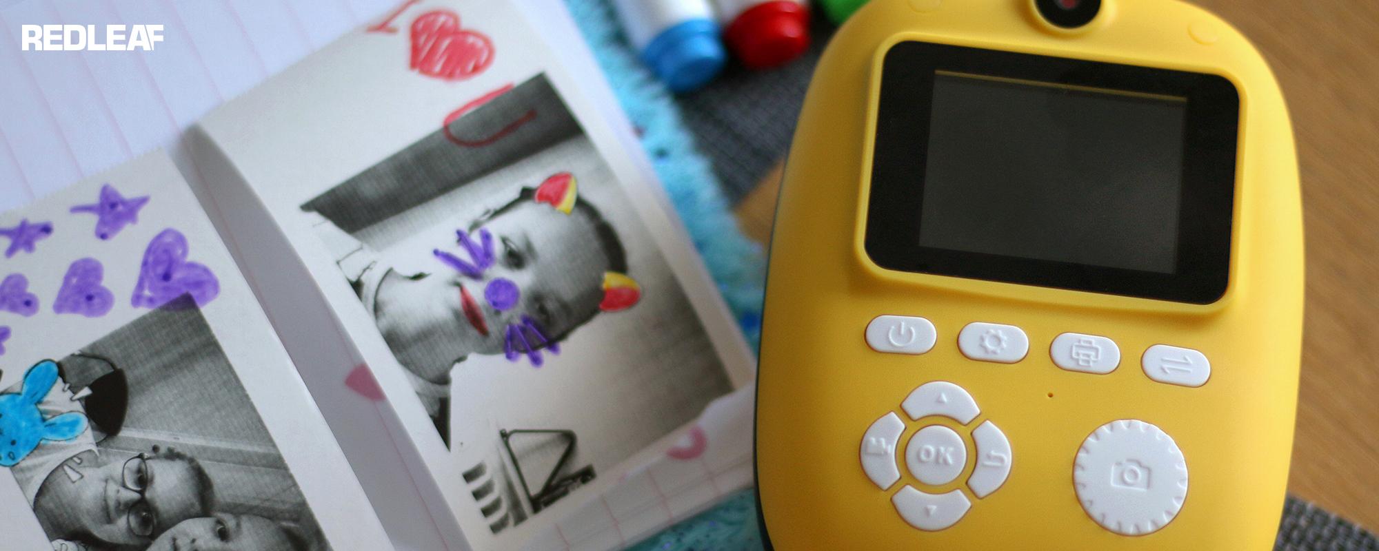Aparat fotograficzny z drukarką dla dzieci Redleaf BOB leżący na biurku z pokolorowanymi mazakami wydrukami