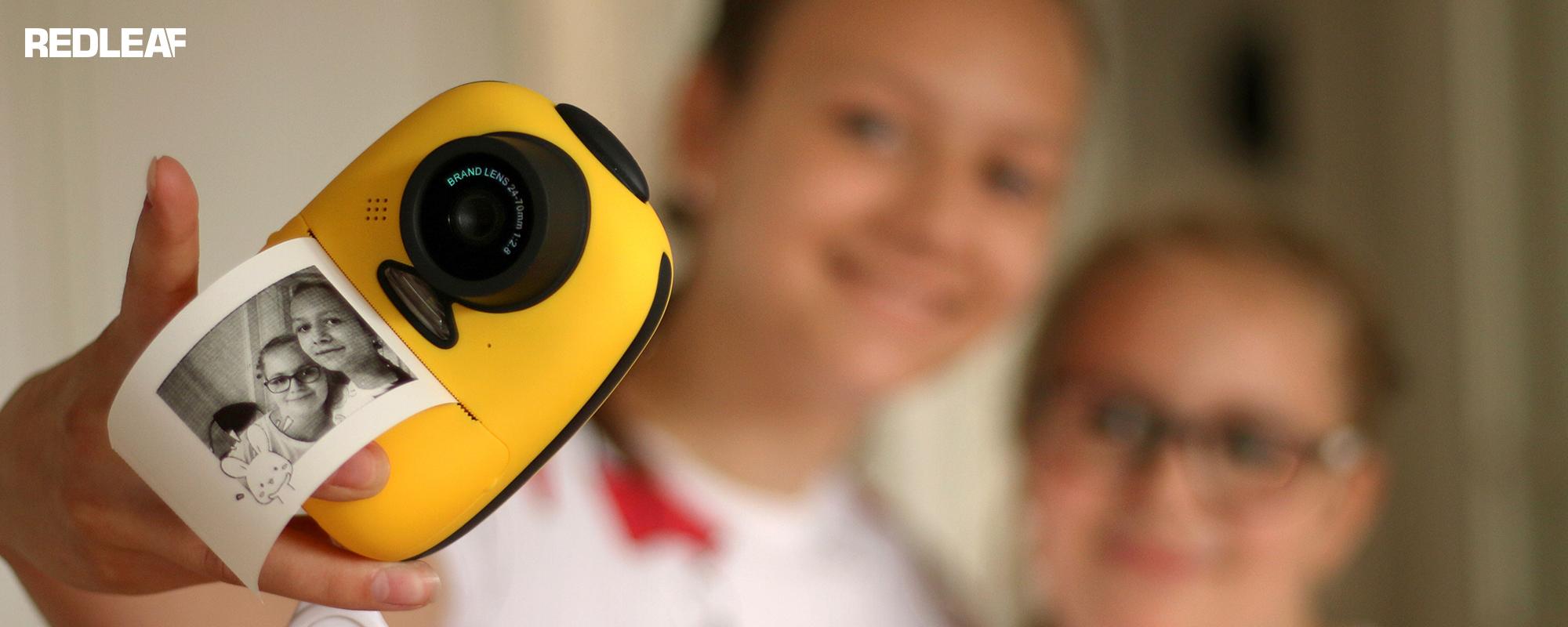 Aparat fotograficzny z drukarką dla dzieci Redleaf BOB w trakcie robienia zdjęcia dwóm dziewczynką