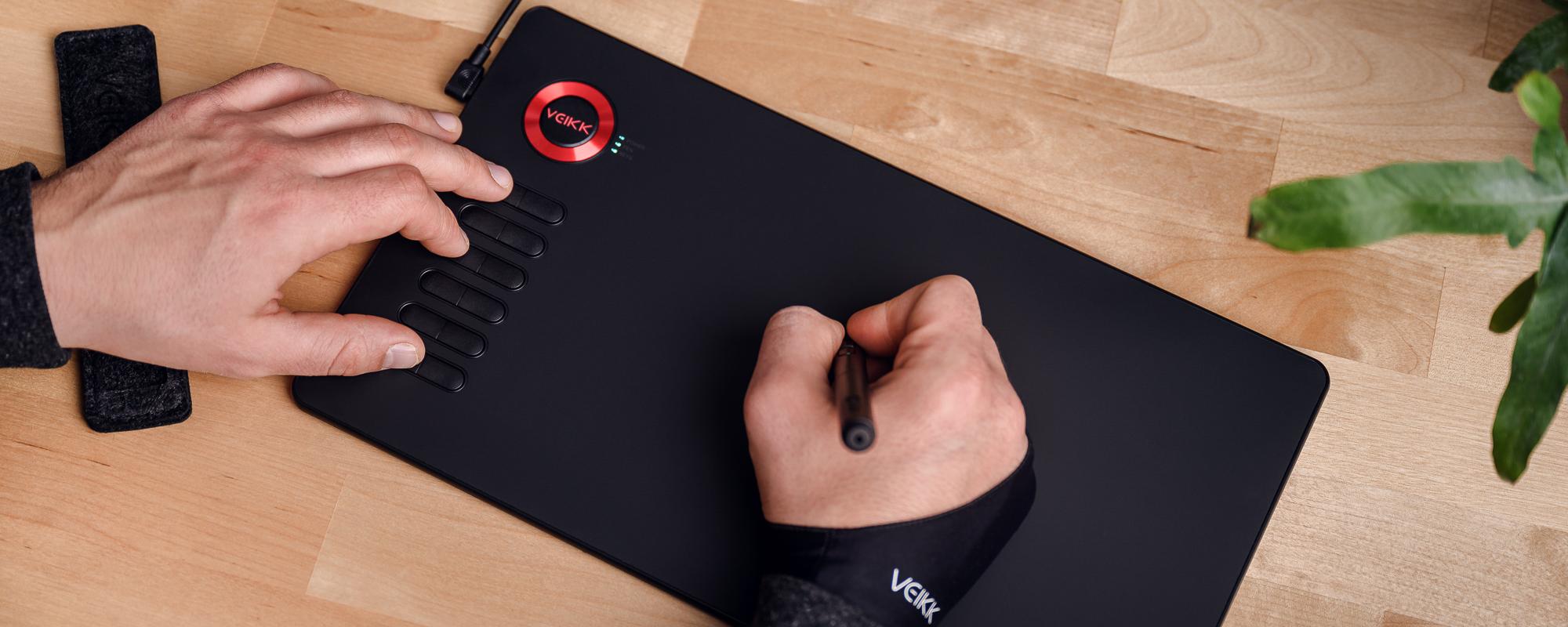 Zdjęcie - tablet graficzny Veikk A15 na jasnobrązowym biurku, lewa dłoń mężczyzny naciska klawisz funkcyjny, prawa obsługuje piórko