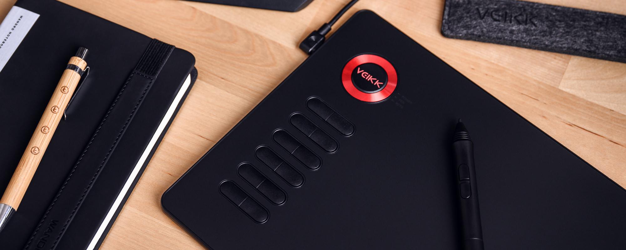 Zdjęcie - tablet graficzny Veikk A15 na jasnobrązowym biurku, piórko, długopis oraz notatnik