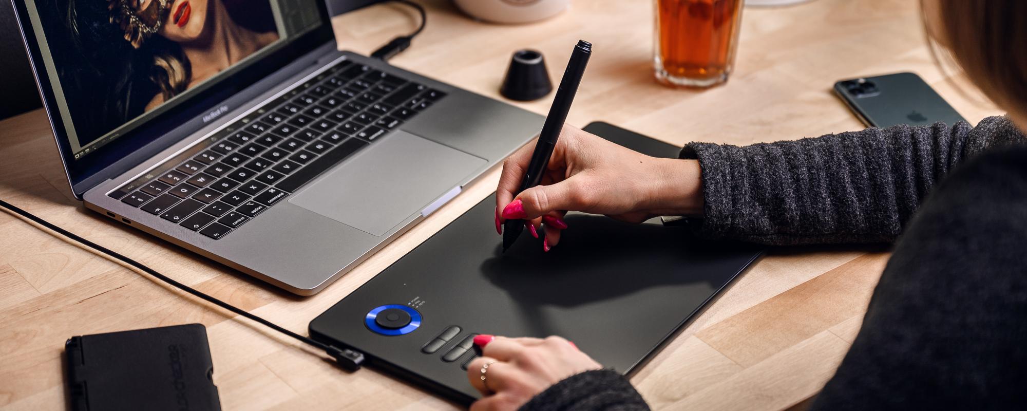 Zdjęcie - tablet graficzny Veikk A15 Pro obsługiwany przez kobietę patrzącą się na monitor podczas pracy