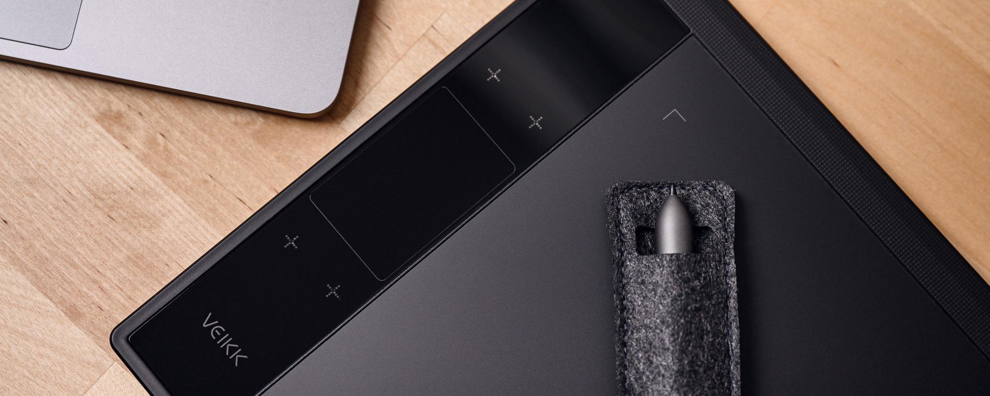 Zdjęcie - tablet graficzny Veikk A30 na jasnobrązowym biurku, a na nim piórko schowane w materiałowy pokrowiec