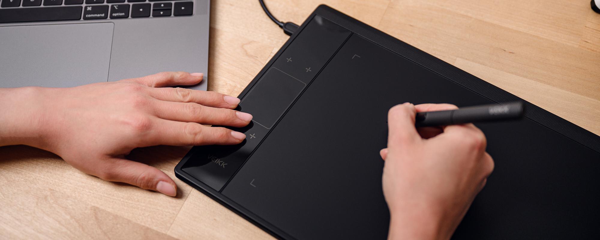 Zdjęcie - tablet graficzny Veikk 30 na jasnobrązowym biurku, lewa dłoń kobiety naciska klawisz funkcyjny, prawa obsługuje piórko pasywne Veikk