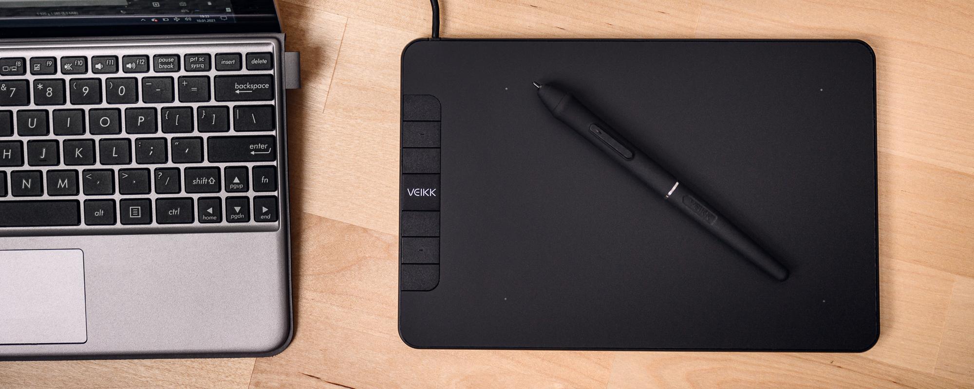 Zdjęcie - tablet Veikk VK640 położony na jasnobrązowym blacie biurka obok laptopa