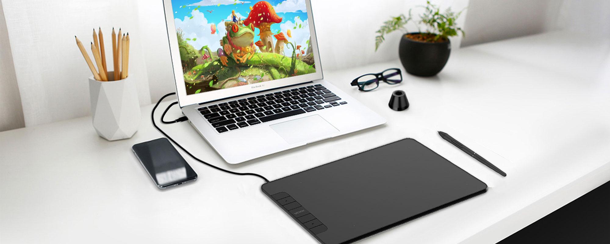 Zdjęcie - tablet graficzny Veikk VK640 wraz z akcesoriami podłączony do laptopa, całość znajduje się na białym blacie biurka