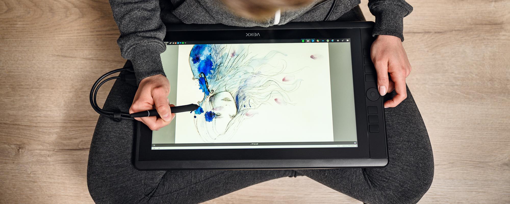 Zdjęcie - kobieta siedząca po turecku obsługuje tablet graficzny z ekranem LCD Veikk VK1560 Pro