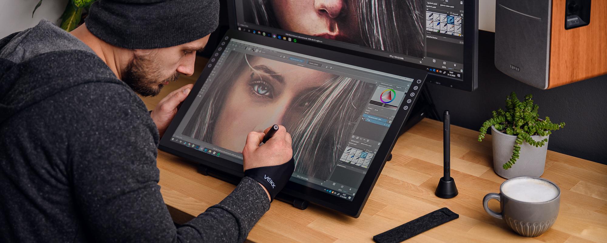 Zdjęcie - młody mężczyzna siedzi przy biurku i obsługuje tablet graficzny z ekranem LCD Veikk VK2200