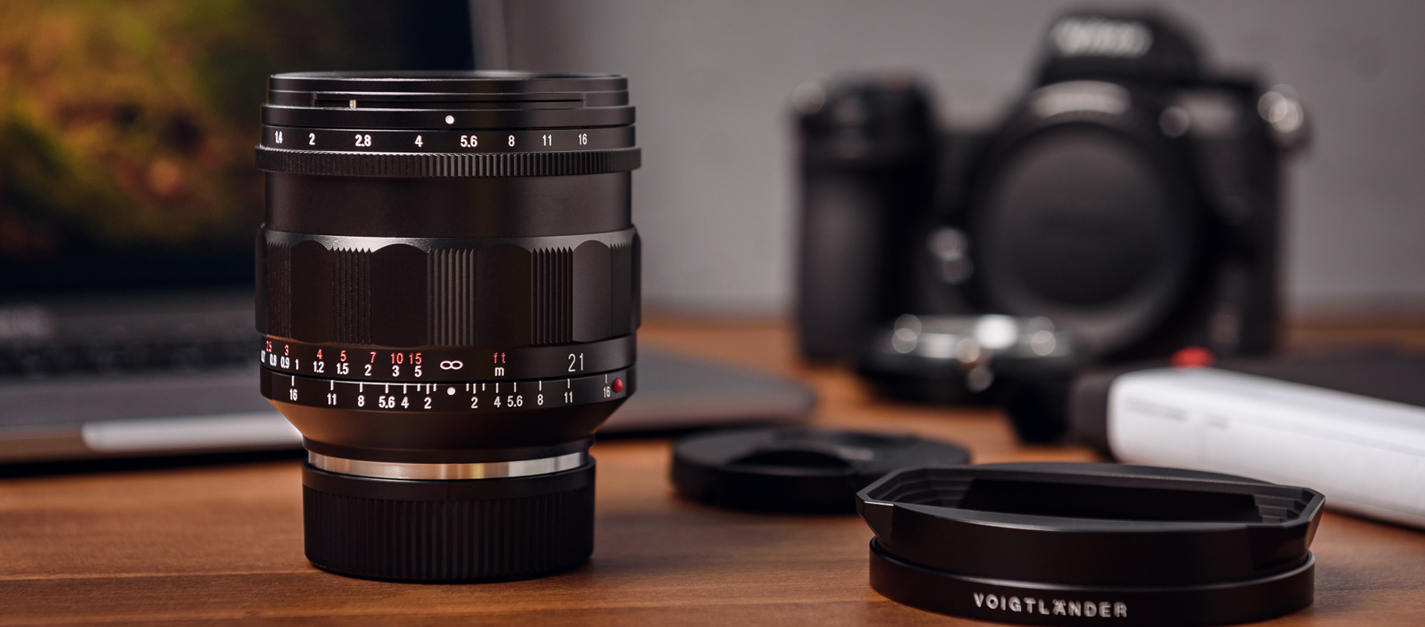 Voigtlander Nokton 21mm f/1.4 lens with Leica M mount on desk with accessories