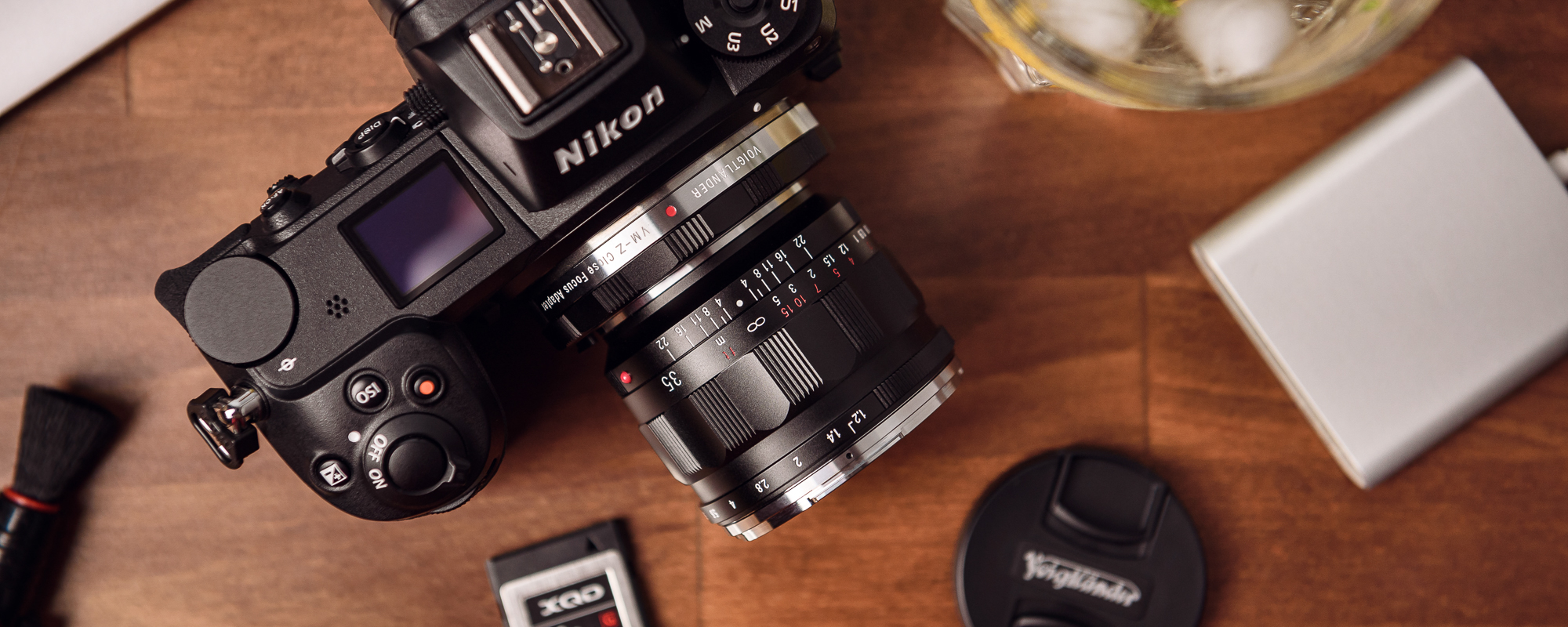 Voigtlander Nokton III 35 mm f/1.2 lens for Leica M on wooden desk attached to Nikon Z6 with adapter