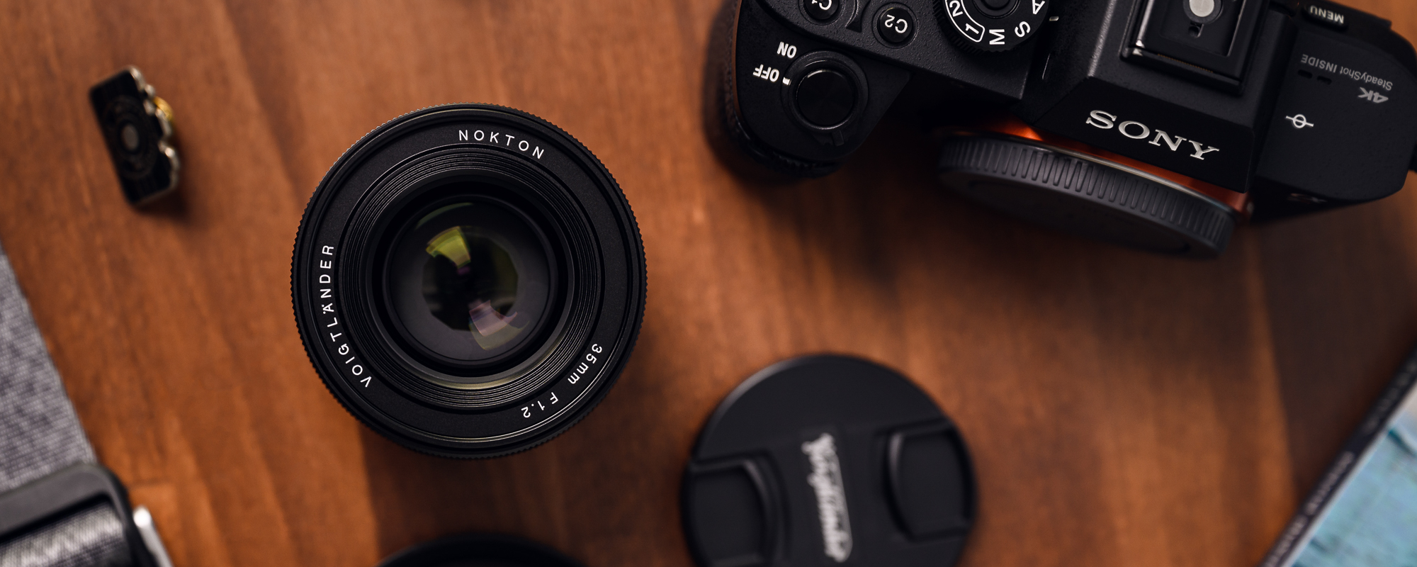 Obiektyw Voigtlander Nokton SE 35 mm f/1,2 do Sony E na drewnianym biurku widok z góry
