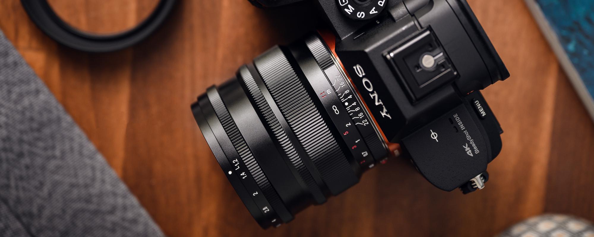 Obiektyw Voigtlander Nokton SE 35 mm f/1,2 do Sony E na drewnianym biurku podpięty do aparatu Sony - widok z góry