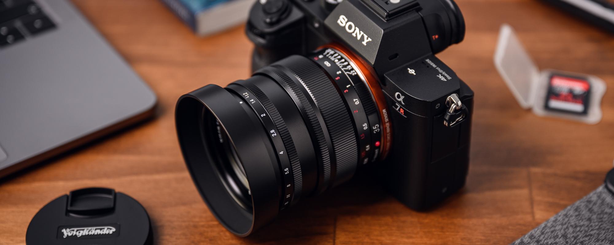 Obiektyw Voigtlander Nokton SE 35 mm f/1,2 do Sony E na drewnianym biurku podpięty do aparatu Sony